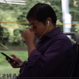 student riding bus, holding phone, rubbing his eyes